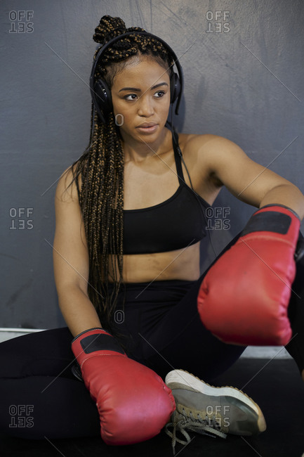 Tired female athlete wearing red gloves listening music while sitting against wall in gym