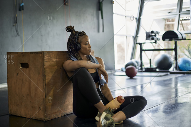 Thoughtful female athlete listening music while sitting on floor in gym