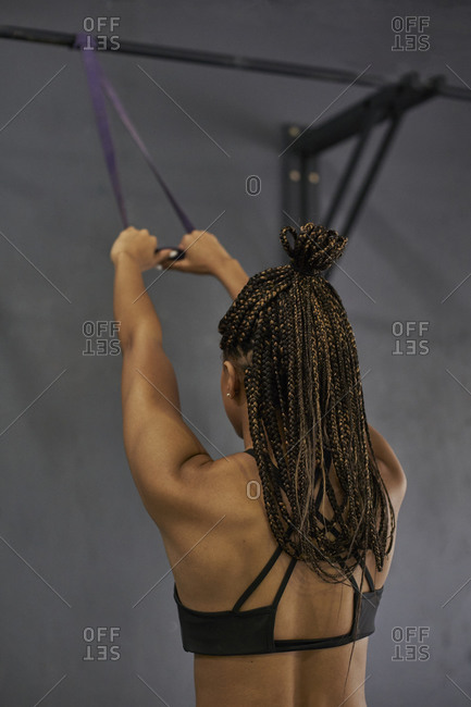 Female athlete with braided hair exercising with resistance band in gym