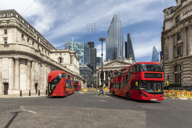 UK- London- Red double decker busses with Bank of England and modern skyscrapers
