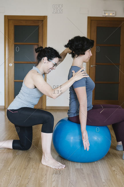 Female physiotherapist assisting patient sitting on fitness ball in health club