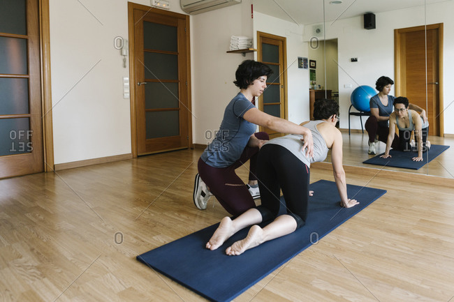 Physiotherapist assisting female patient in exercising on mat at health club