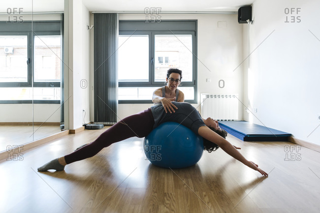 Physiotherapist assisting patient in lying on fitness ball at health club
