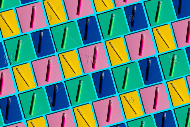 Pattern of colorful notebooks and matching felt tip pens