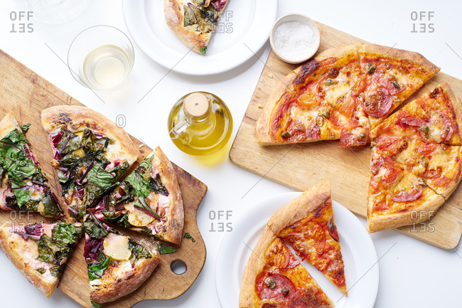 Overhead image with vegetarian apple and beetroot pizza and salami pizza