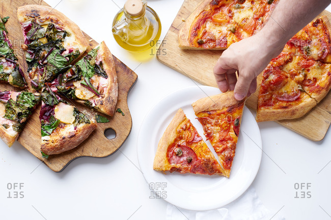 Male hand holding a slice of pizza with salami