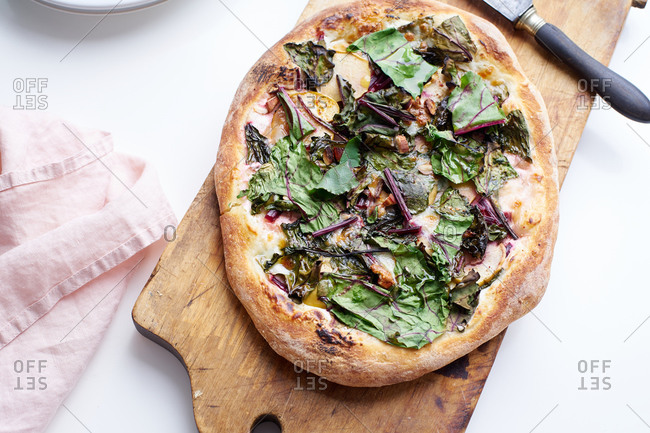 Sliced vegetarian pizza with beet leaves, almonds, apples and mozzarella
