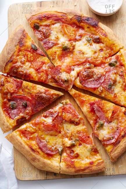 Top view image of pizza with salami, tomato sauce and capers