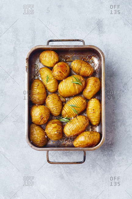 Crispy roasted potatoes with rosemary butter and garlic. Top view in a baking tray