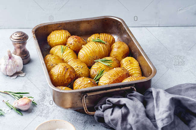 Crispy roasted potatoes with rosemary butter and garlic in baking tray