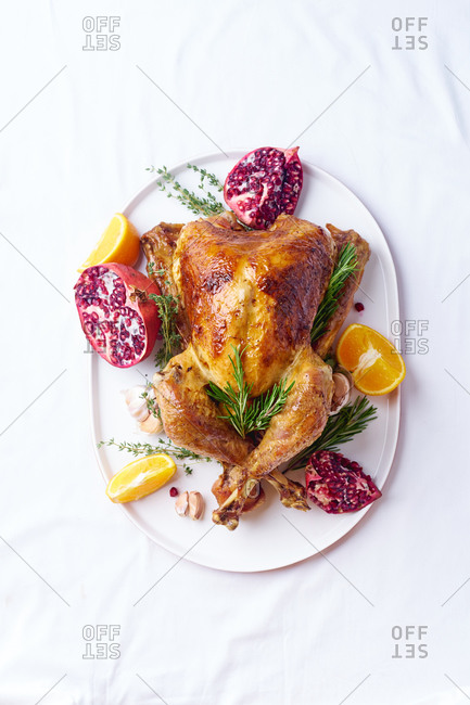 Top view of garnished turkey on a platter with pomegranate and rosemary