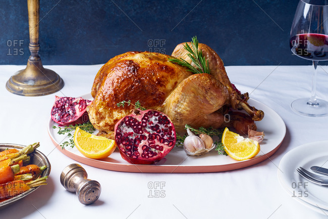 Garnished turkey on a platter with pomegranate, orange and rosemary next to blue background