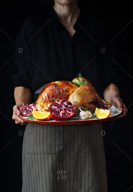 Woman holding a platter with roasted turkey cooked and garnished for Thanksgiving.