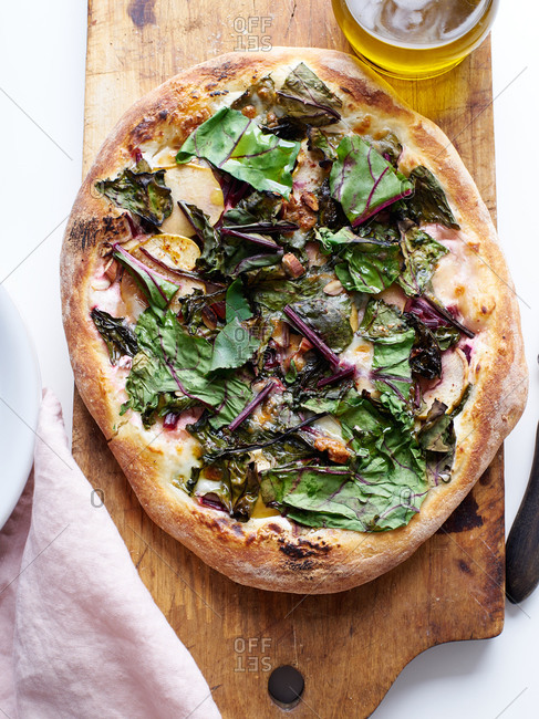 Vegetarian pizza with beet leaves, almonds, apples and mozzarella