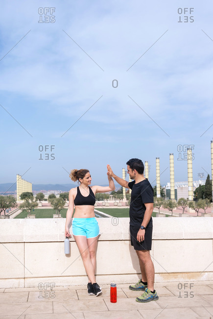 Couple of runners clapping hands while talking after exercise