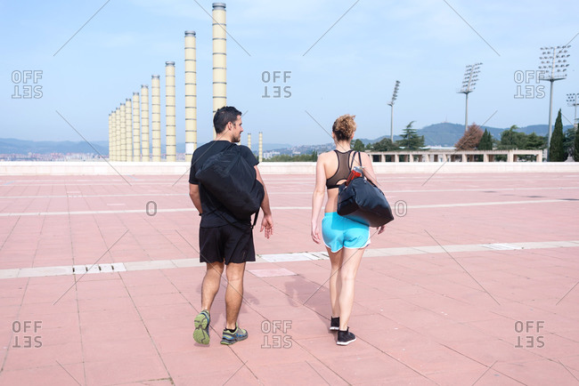 Back view of a couple talking while walking before running