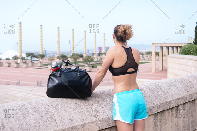 Beautiful caucasian female athlete with gym bag looking away smiling.