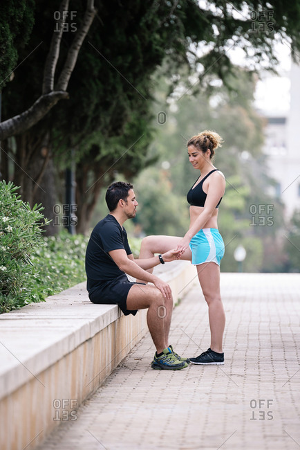 Happy running couple taking a break after running and talking