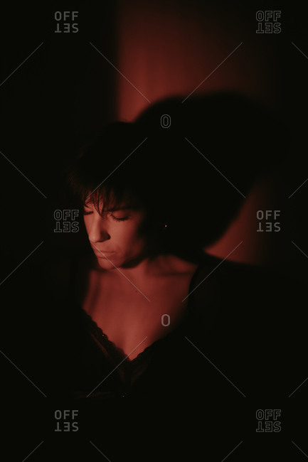 Portrait of a woman with short hair and her eyes closed in the darkness and under red light