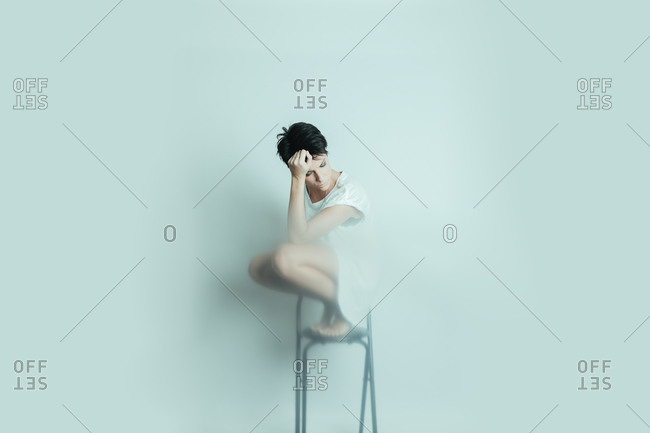 Young and attractive woman crouched on a stool looking down worried with her head resting on her hand in studio