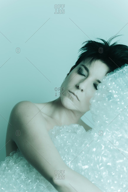 Portrait of an attractive woman with short hair and her eyes closed, resting her head over bubble wrap plastic in studio