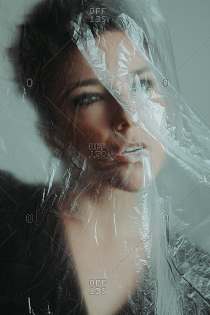 Portrait of a thoughtful attractive woman with short hair covered in plastic in studio