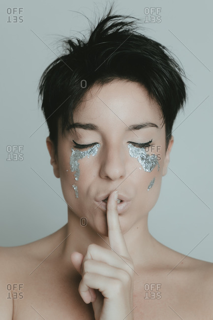 Creative portrait of an attractive woman with short hair and with her eyes closed covering her lips with her finger