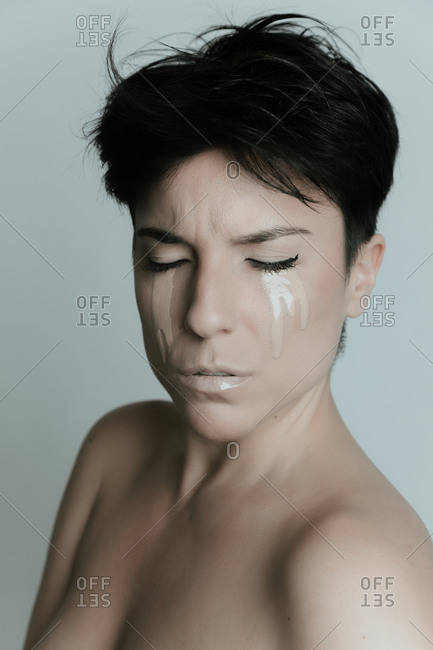 Creative portrait of an attractive woman with short hair and with her eyes closed crying make up in studio