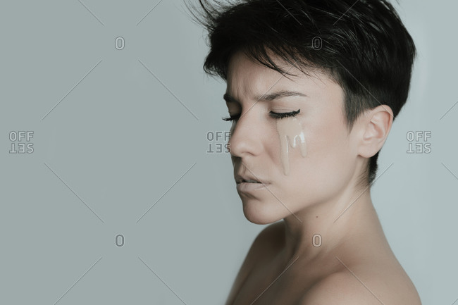 Creative portrait of the profile of an attractive woman with short hair and with her eyes closed crying make up in studio
