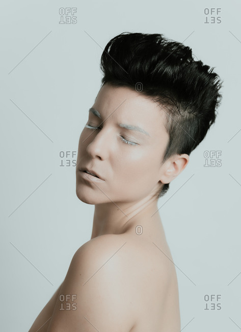 Creative portrait of the profile of an attractive woman with short hair and with her eyes closed wearing artistic white make up in studio