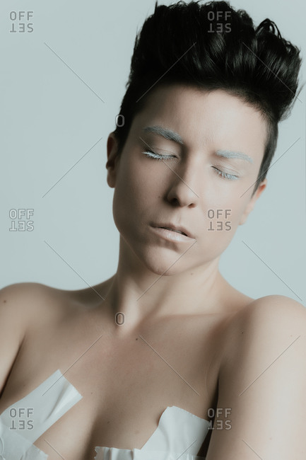 Creative portrait of an attractive woman with short hair and with her eyes closed wearing artistic white make up and tape over her breasts in studio