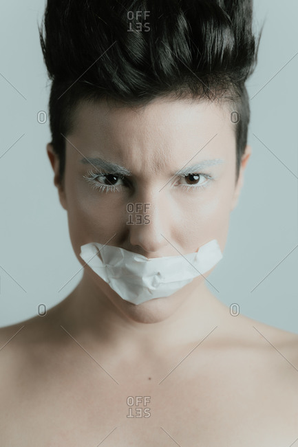 Creative portrait of a serious and attractive woman with short hair looking at camera wearing artistic white make up and tape over her mouth in studio