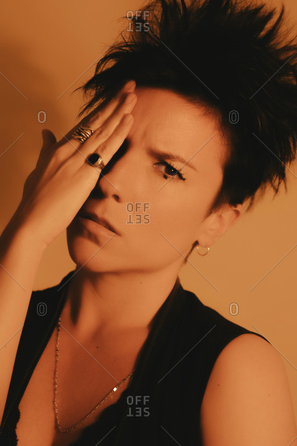 Portrait of an attractive and serious woman with short hair looking away with her hand covering one eye wearing an artistic make up in studio with orange gel lighting