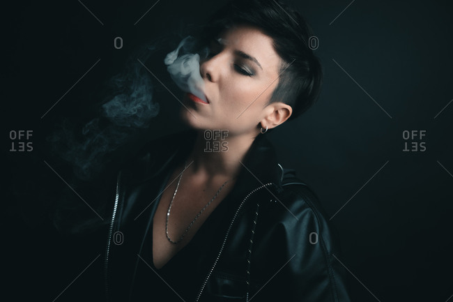 Attractive woman with short hair and red lips with her eyes closed smoking with a black leather jacket and a black backdrop in studio