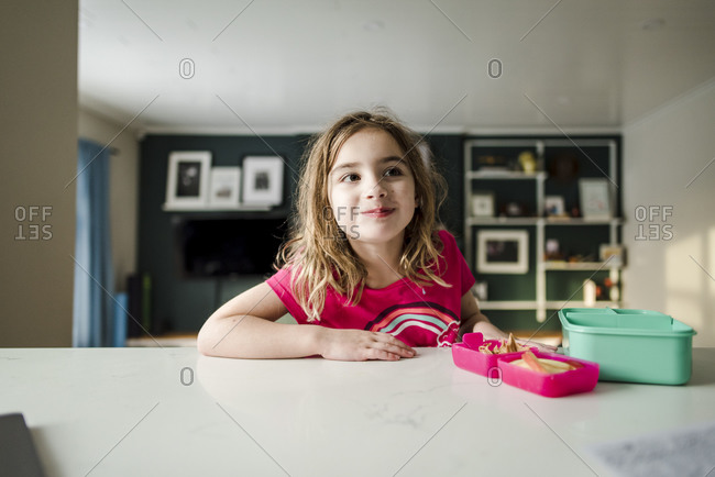 Young girl sitting at kitchen counter eating lunch