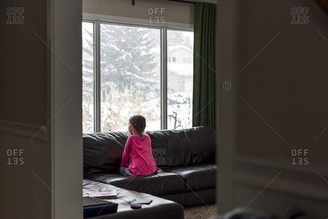 Rear view of young girl sitting on sofa looking out window at snow