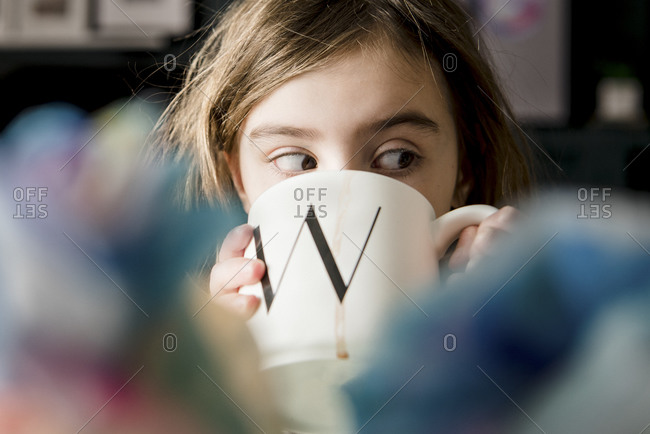 "Close up of a young girl drinking from a large mug with a ""W"""