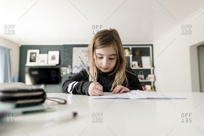 Little girl sitting in kitchen doing homework