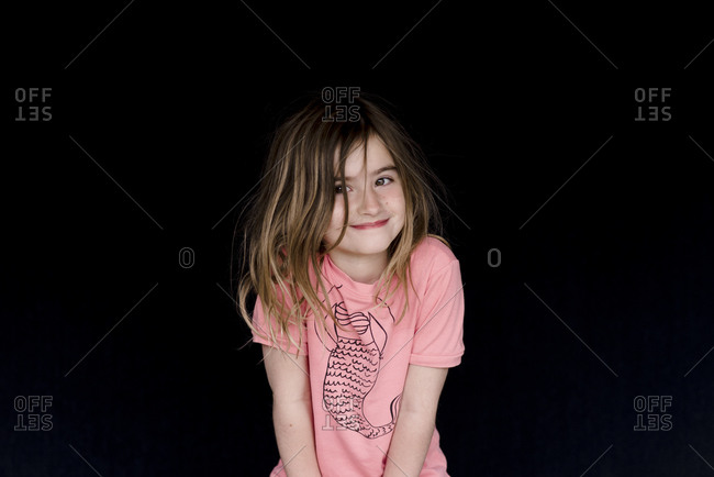 Portrait of a sweet young girl wearing a pink mermaid t-shirt in front of dark background