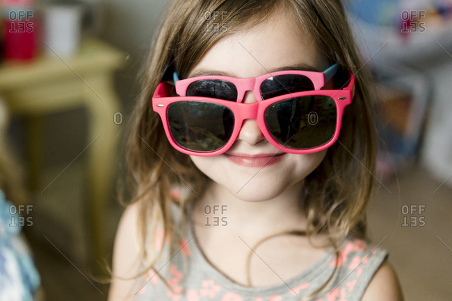 Young girl trying on two pairs of sunglasses at once