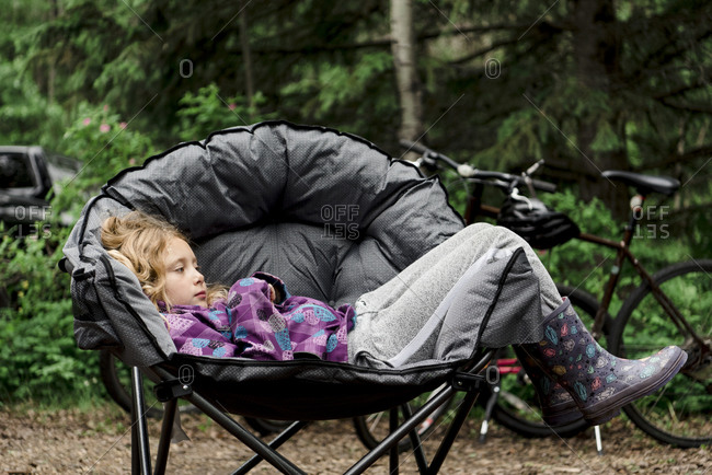Young girl relaxing in folding sauce chair while camping