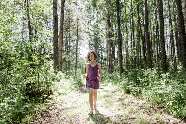Young girl hiking through the woods in summertime