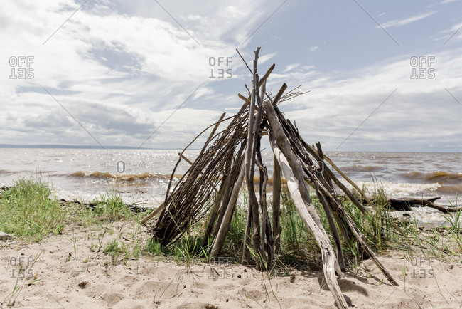 Sticks in the shape of a teepee on the ocean shore