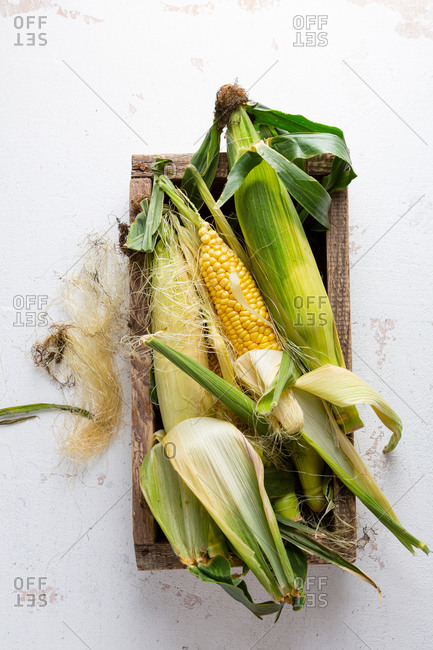 Overhead view of corn on the cob in wooden crate