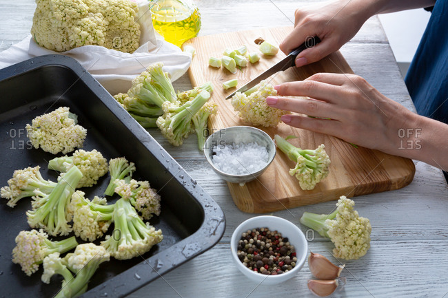 Woman cutting and cooking cauliflower for vegan dish