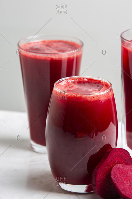 Sweet beet root juice served in a glass on a white marble countertop