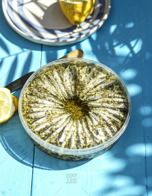 Anchovies in olive oil on blue table outdoors