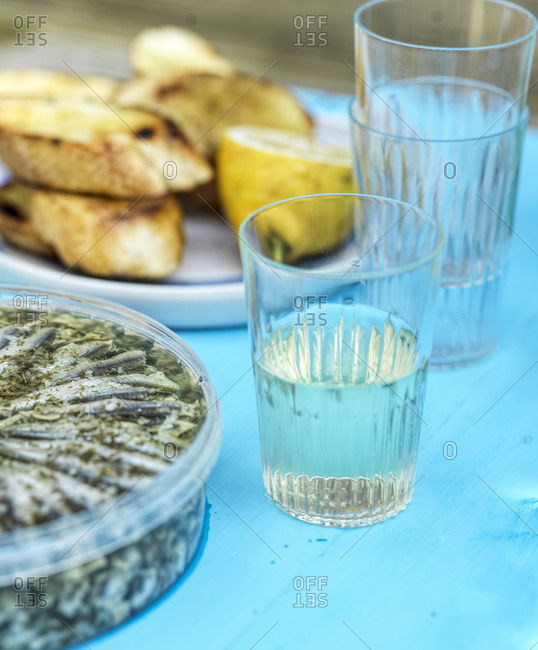 Glass of white wine on table outdoors beside anchovies
