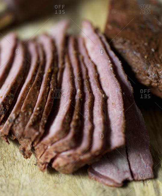 Sliced tri tip steak on wood board