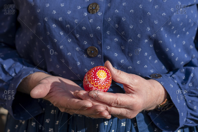 A woman holds a Sorbian Easter egg in her hand. It was decorated with the wax batik technique.